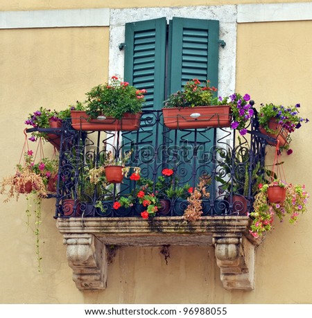 Old balcony with flowers and plants - stock photo