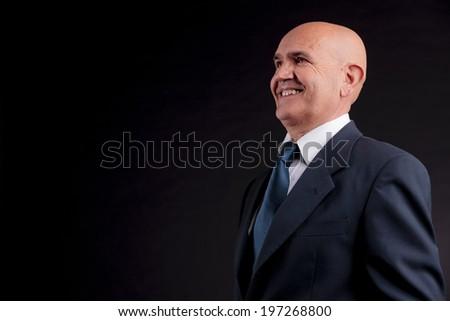 old bald self-confident businessman on a dark background - stock photo