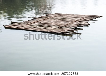 Old bamboo raft is floating on the lake in the morning. - stock photo