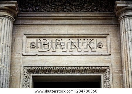 Old bank sign engraved in stone or concrete above the door of financial building concept for finance and business - stock photo