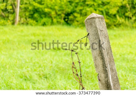 old barb wire with concrete pillar