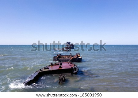 Old barges remaining on the ruins of the pier into the sea. - stock photo