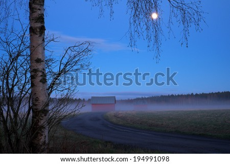Old barn and country road in the moonlight. - stock photo