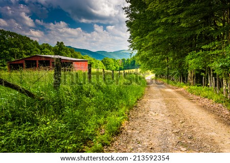 Old barn and farm fields along a dirt road in the rural Potomac Highlands of West Virginia. - stock photo