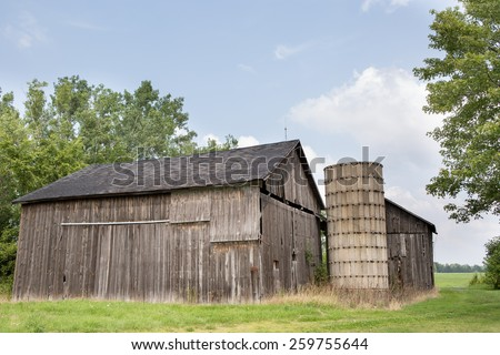 Old barn and silo with a blue sky. - stock photo