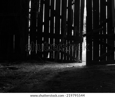 Old barn door with light beaming in - stock photo