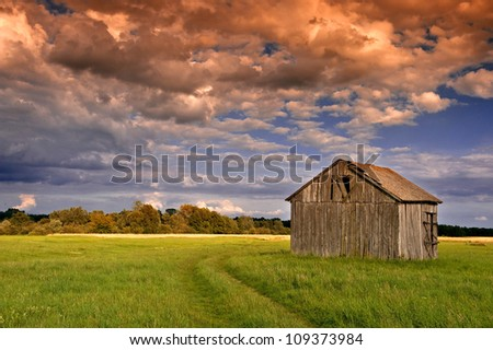 old barn on field in the sunset - stock photo