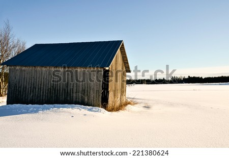 Old barn out on a snowy field - stock photo
