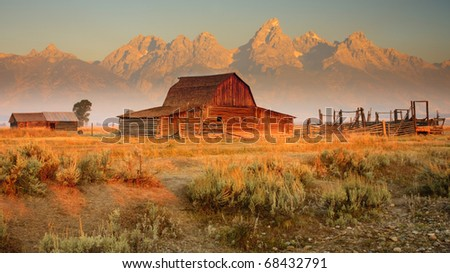 Old barn sits in front of the Grand Teton Mountains, Wyoming. - stock photo