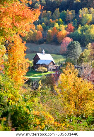 Old barn surrounded by autumn trees in Vermont country side