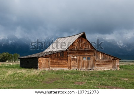 Old Barn Under Rainy Cloudy Skies - stock photo