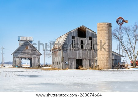 Old barns with a silo and windmill stand in a snowy Indiana landscape. - stock photo