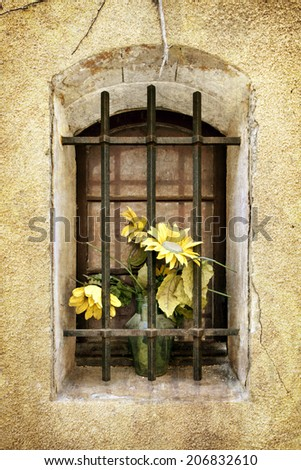 Old barred window with dusty flower arrangement.  Grunge effects.  Provence, France. - stock photo