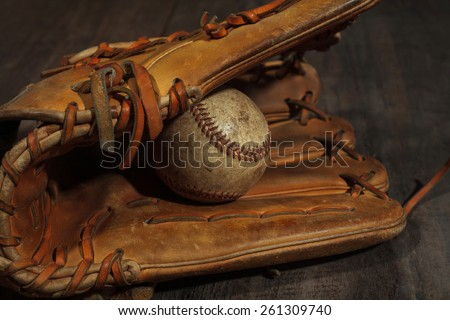 Old baseball glove with weathered baseball on wood background - stock photo
