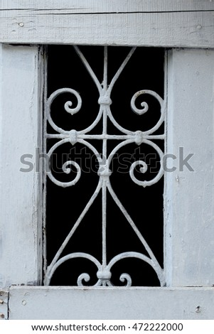 Old basement window wooden frame with decorative metal pattern. Abstract background.