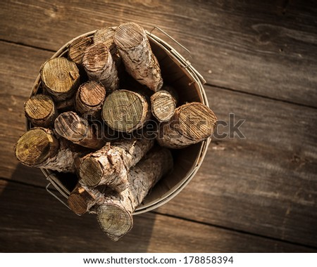 Old Basket of Cut Firewood on Rustic Wood Floor - stock photo