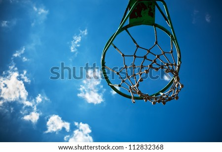 Old basketball basket with a cloudy blue sky in the background. - stock photo