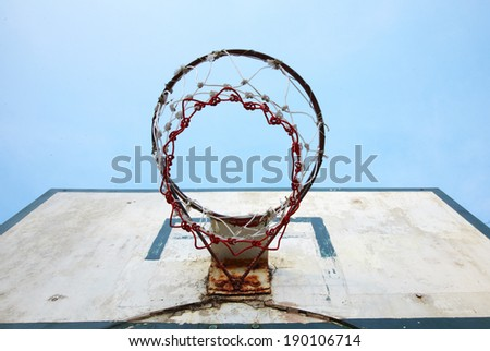 old basketball board and blue sky in sun light - stock photo