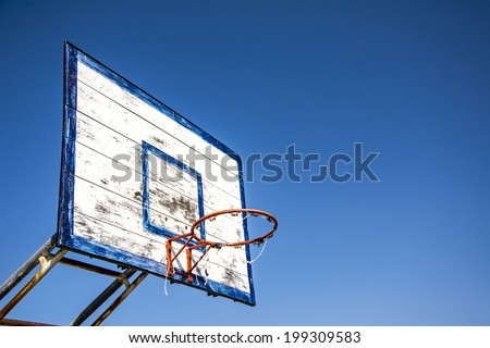 Old basketball hoop and board on blue sky
