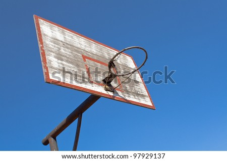 Old basketball hoop over blue sky