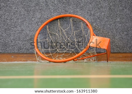Old basketball hoop with net the floor of a school gym - stock photo