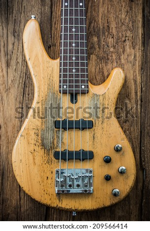 old bass guitar on wooden background - stock photo