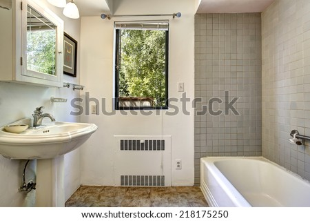 Old bathroom in white and grey color with washbasin stand, cabinet with mirror and bath tub