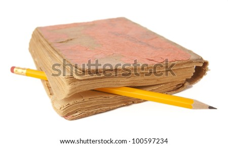 old battered   red notebook with  yellow pencil