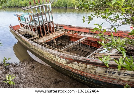 Old beached fishing Boat - Krabi River, Thailand - stock photo