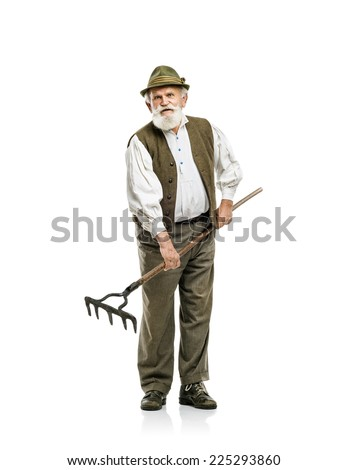Old bearded bavarian man in hat holding rake in his hand, isolated on white background - stock photo