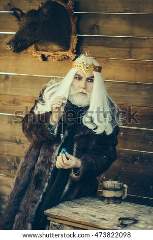 Old bearded man wizard in golden crown with long white hair and beard holding blue gem stone and silver pendant for hypnosis on wooden background
