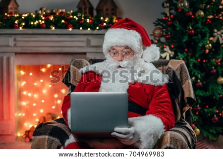 old bearded santa claus using laptop while sitting in armchair