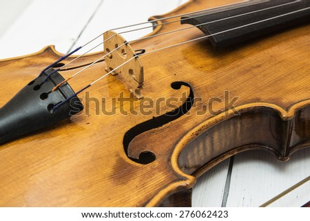 Old beautiful violin close-up on a white wooden background