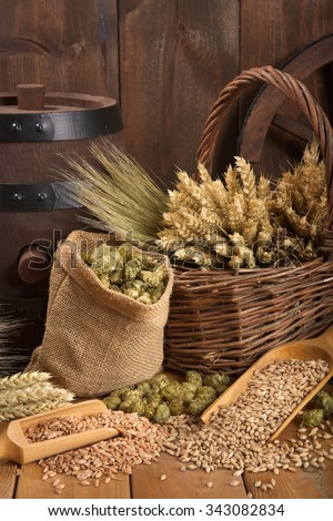 old beer barrel with hops, wheat, grain, barley and malt - stock photo