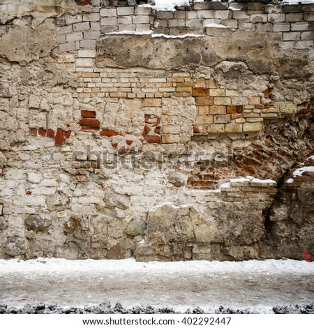 Old beige wall and a ground covered with snow