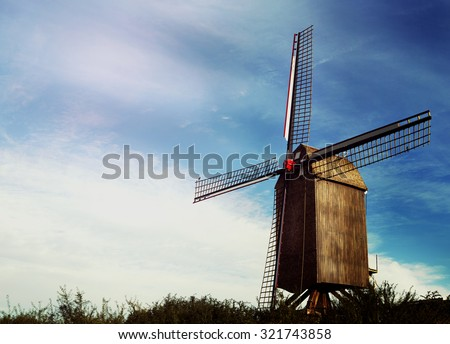 old Belgian windmill standing on the summer meadow against blue sky - stock photo