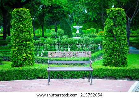 old bench between two bushes in the formal garden - stock photo