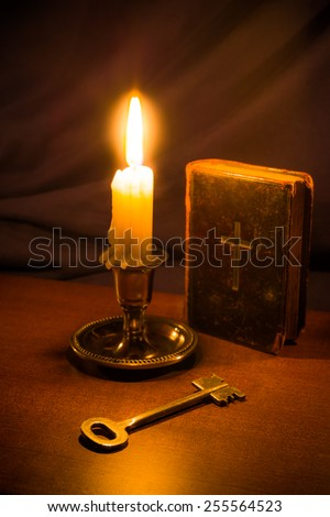 Old bible and candle with key on a wooden table. Focus on the key, image vignetting and in yellow, soft toning