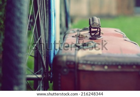 Old bicycle and old brown suitcase with a retro effect - stock photo