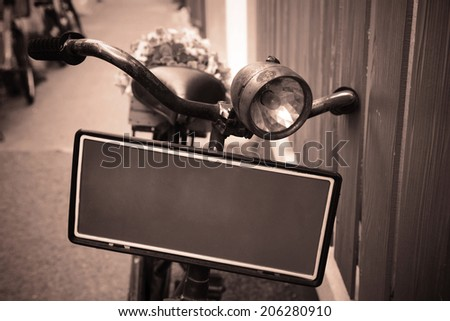 Old bicycle carrying flowers for decoration by Vintage stylized photo - stock photo