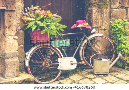 Old bicycle decorated with flowers on the street - stock photo