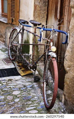 Old bicycle on a medieval street in France - stock photo