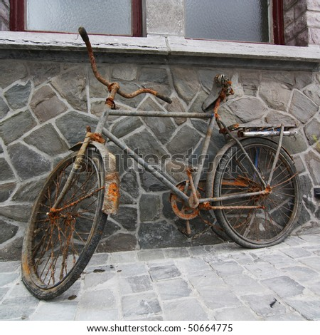 Old bicycle on a stone wall...