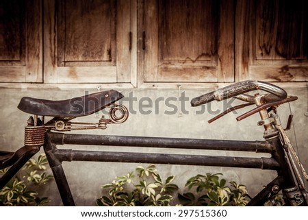 Old bicycle on wooden window house wall in vintage color tone - stock photo