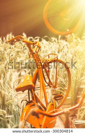 Old bicycle painted in orange in a old street. - stock photo