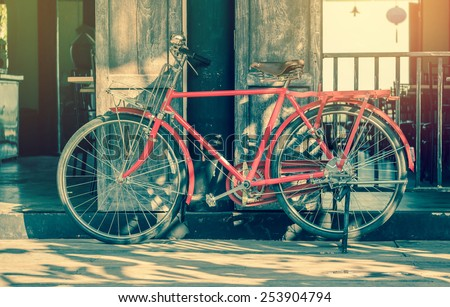 Old bicycle parked near a house. - stock photo