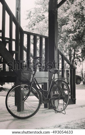 Old bicycle vintage park  with old wooden building Structure background (toned picture)