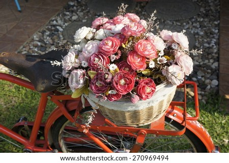 old bicycle with basket of flowers - stock photo