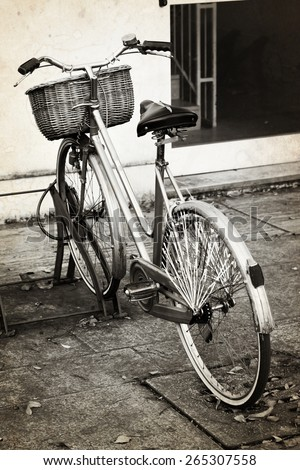 Old bicycle with wicker basket. Aged photo effect has been applied. - stock photo