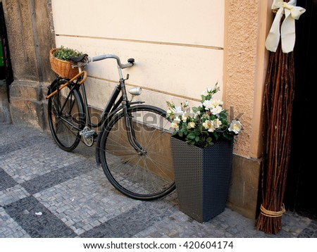 Old bicycle with wicker basket on the street - stock photo
